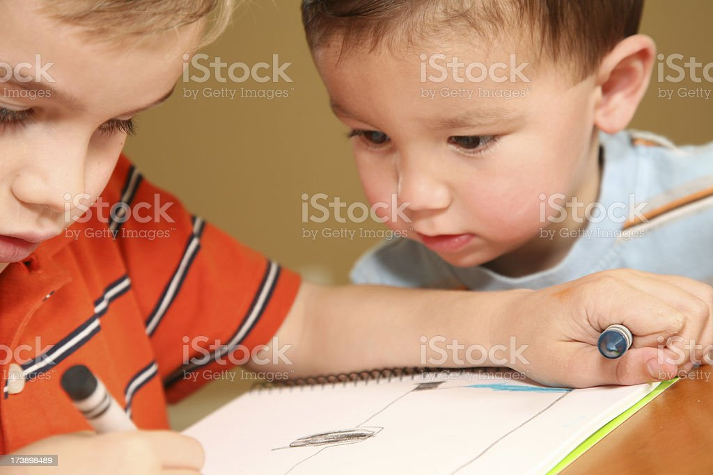 Sibling closely watching his brother's work royalty-free stock photo