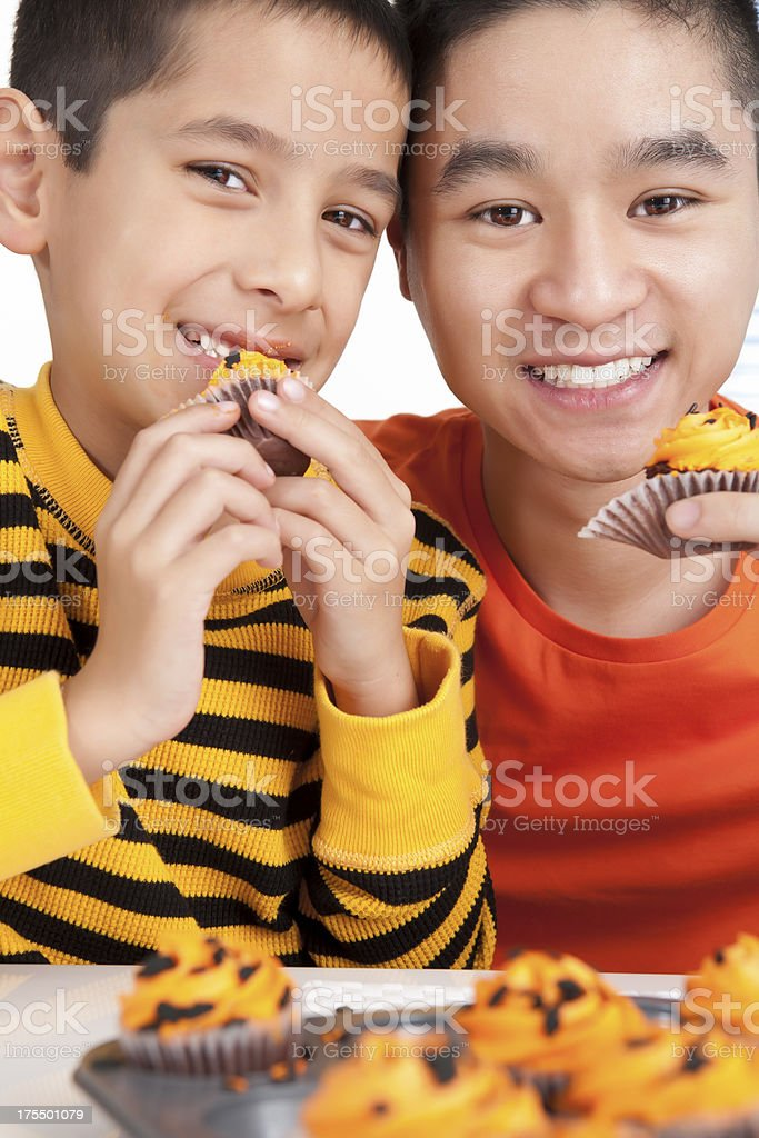 Sibling eating halloween cupcakes royalty-free stock photo