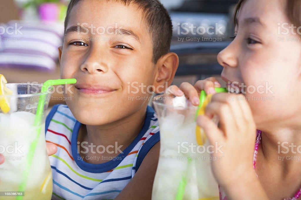 Sibling enjoying lemonade outdoor stock photo