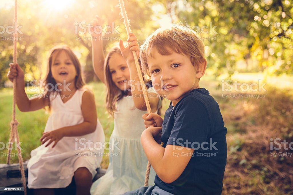 Sibling in tire swing stock photo