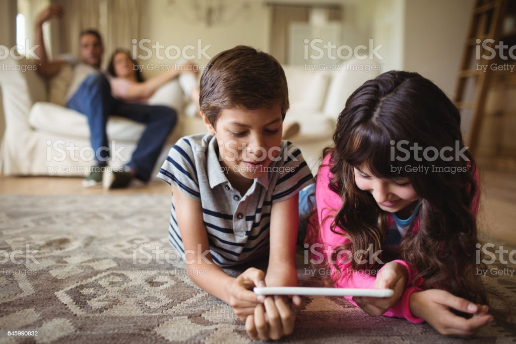 Sibling lying on rug and using digital tablet in living room stock photo