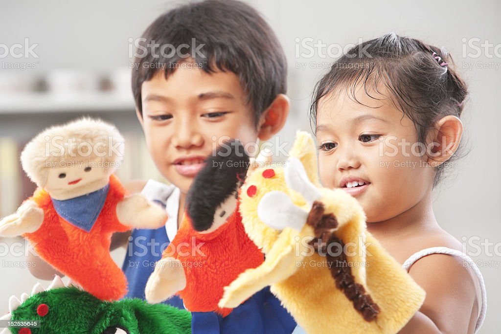 Sibling playing hand puppet stock photo
