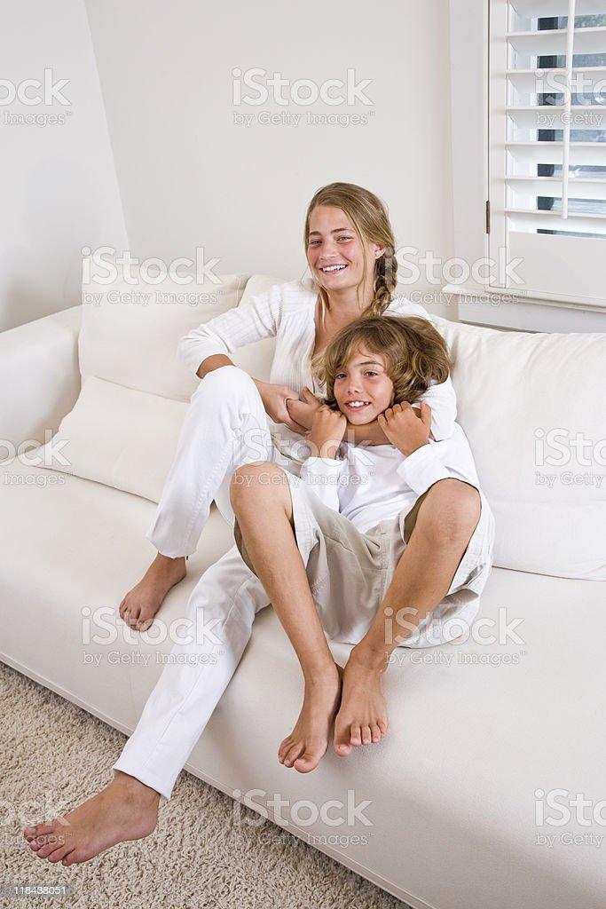 Hermanos en su hogar mientras se relaja en el sofá blanco foto de stock libre de derechos