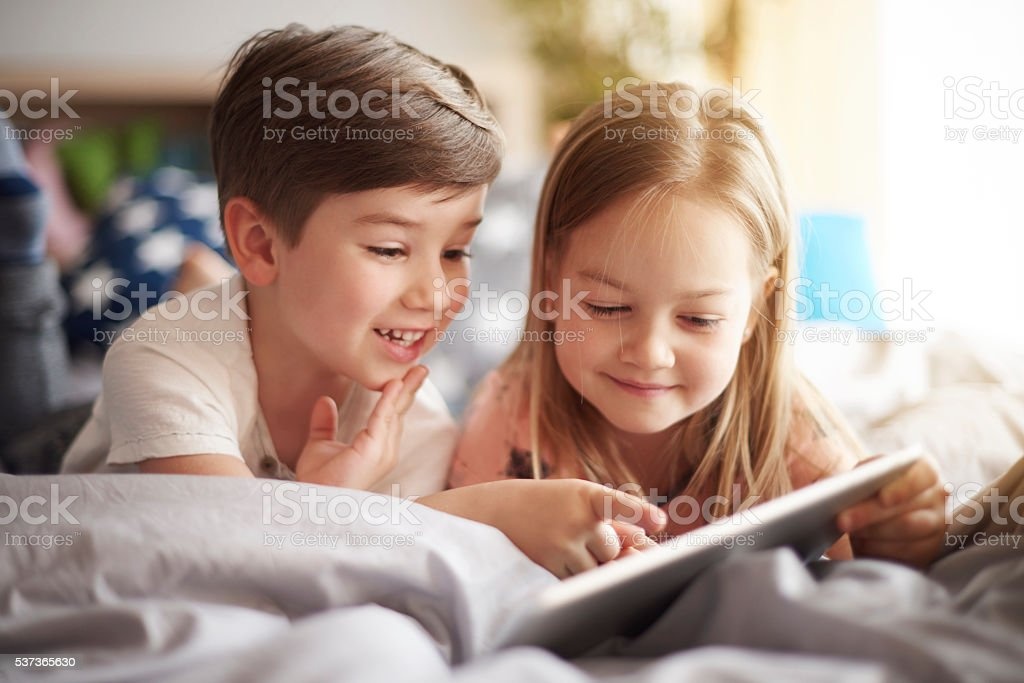 Siblings browsing a digital tablet stock photo