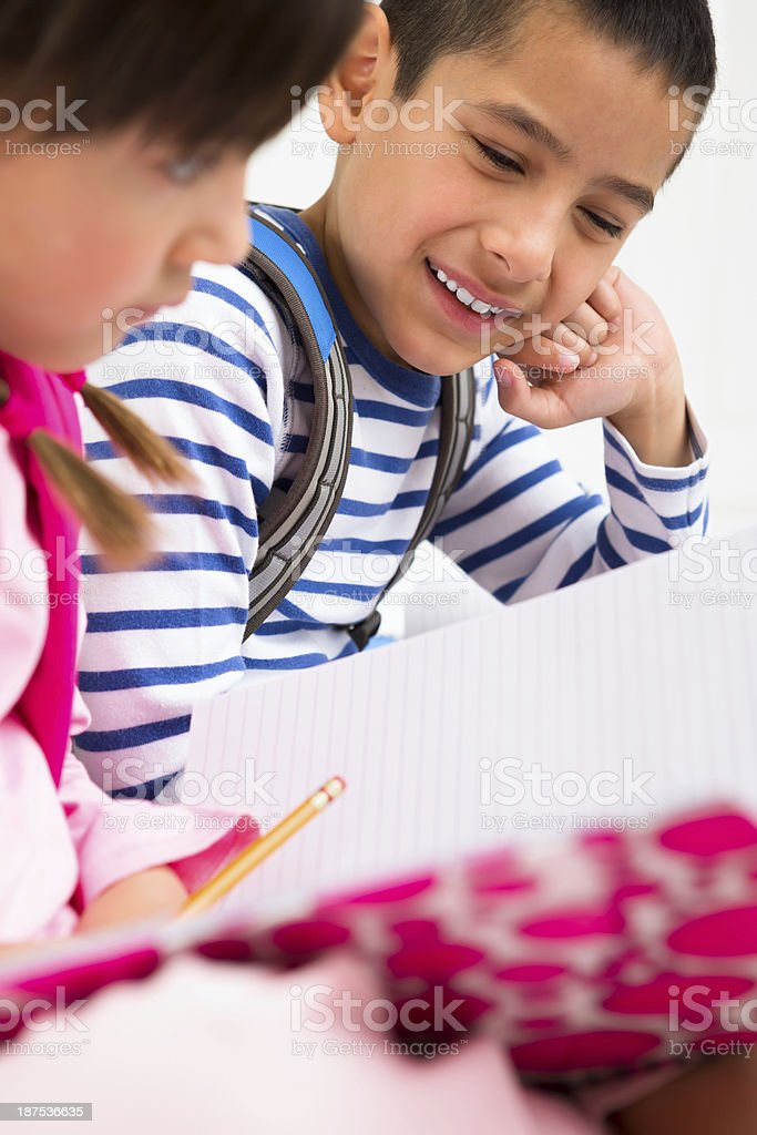 Siblings doing homework together stock photo