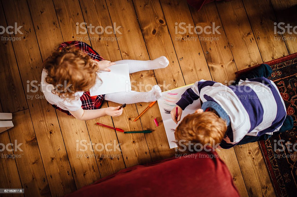 Siblings Drawing Together stock photo