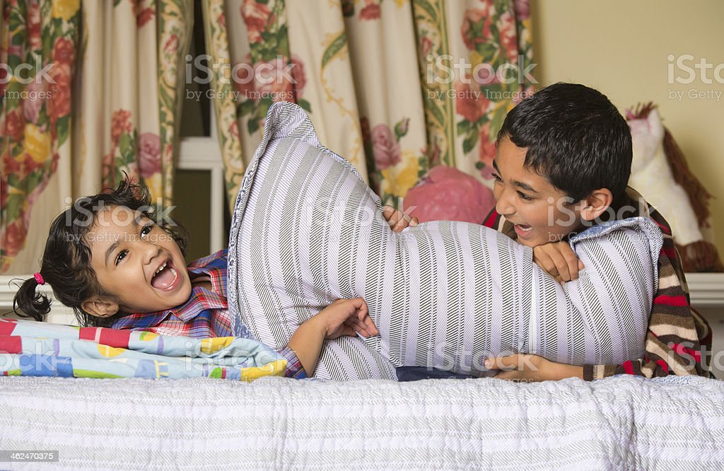 Siblings Enjoying a Pillow Fight stock photo