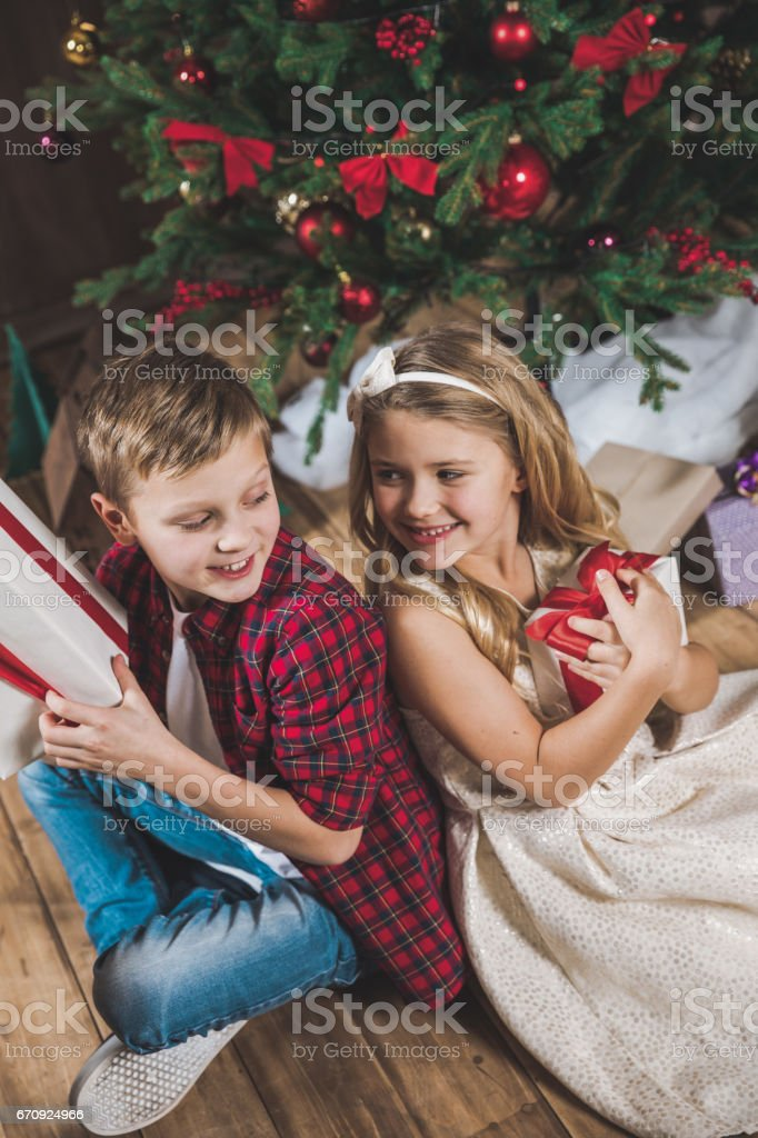 Siblings holding gift boxes stock photo