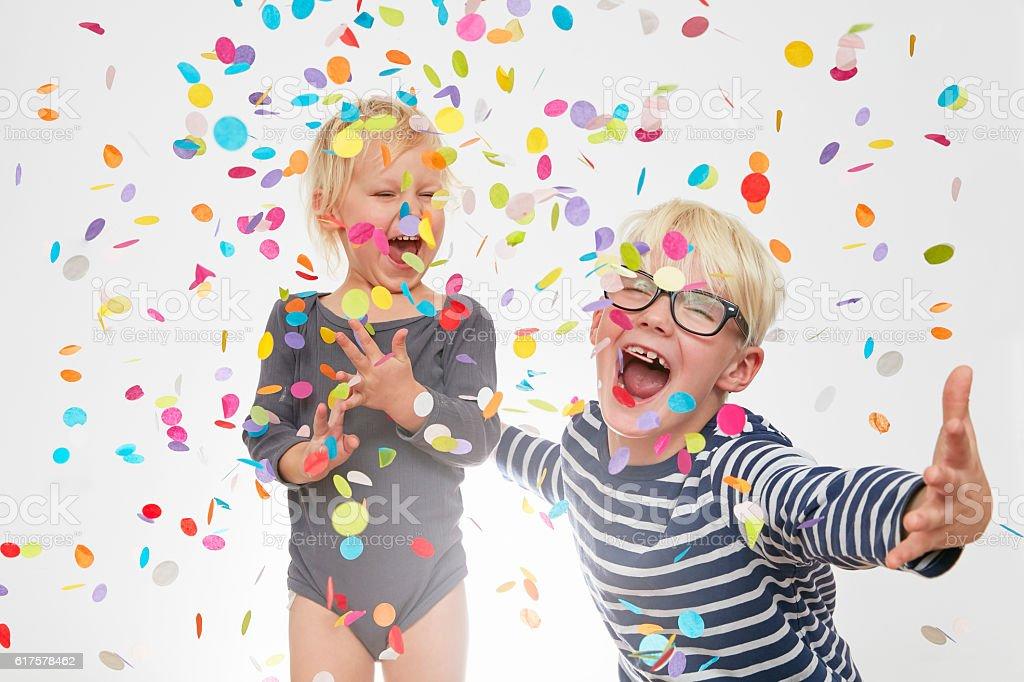 Siblings in confetti stock photo