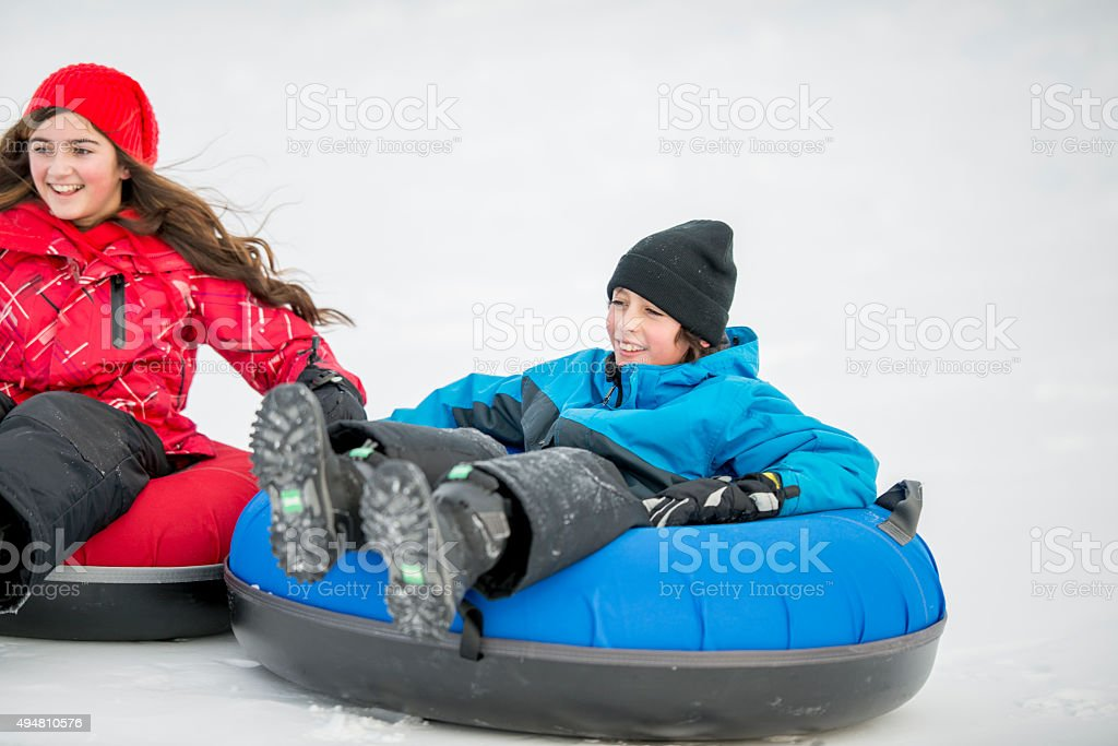 Siblings Inner Tubing Down a Sledding Hill stock photo