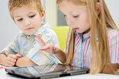 Siblings on the table using digital tablet