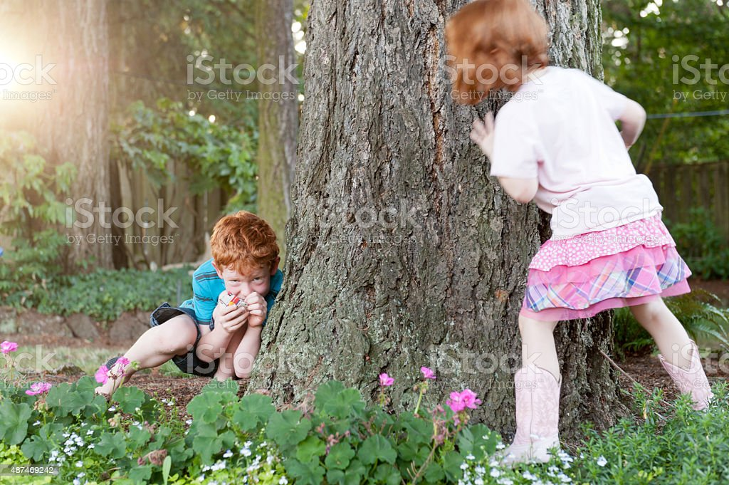 Siblings play hide and seek in backyard stock photo