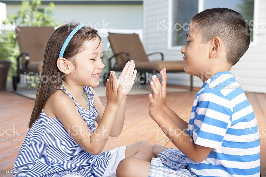 Siblings playing clapping games stock photo
