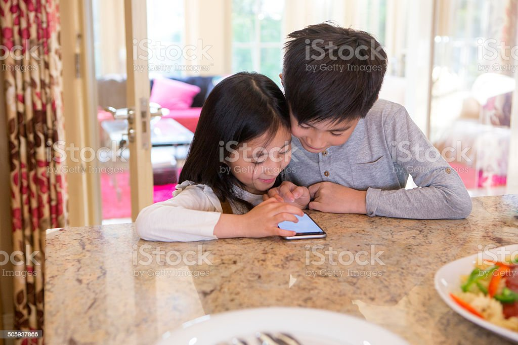 Siblings Playing On A Smart Phone stock photo