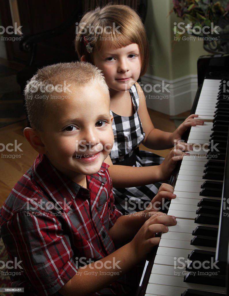 Siblings Playing the Piano stock photo