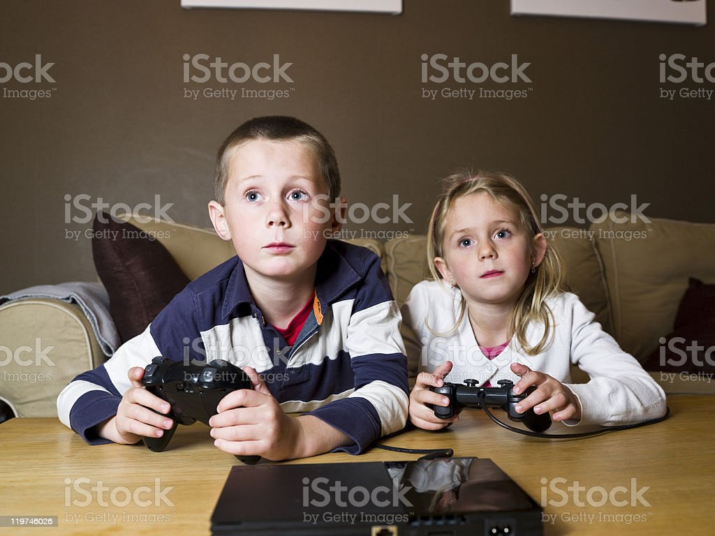 Siblings playing video games stock photo