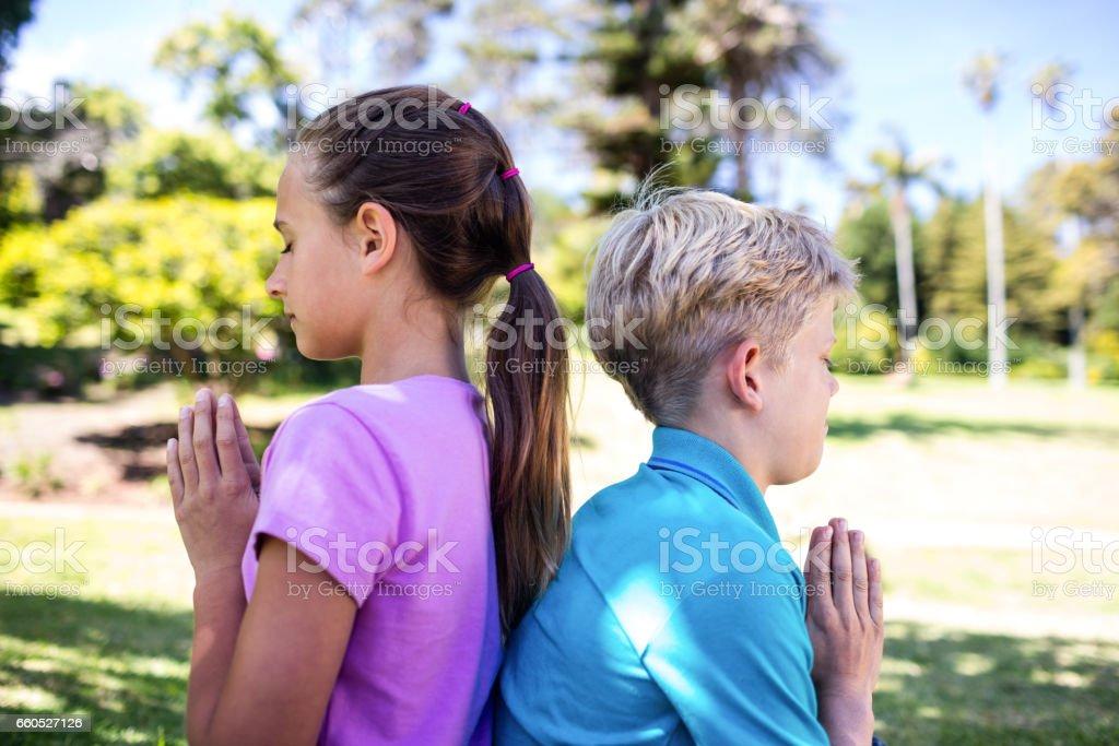 Siblings praying in park stock photo
