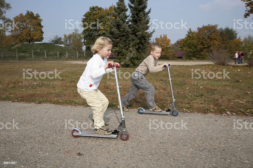 Siblings Pushing Scooters royalty-free stock photo