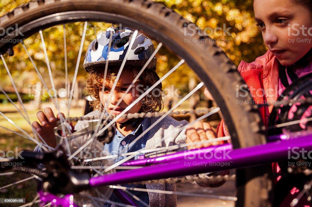 Siblings repairing mountain bike stock photo