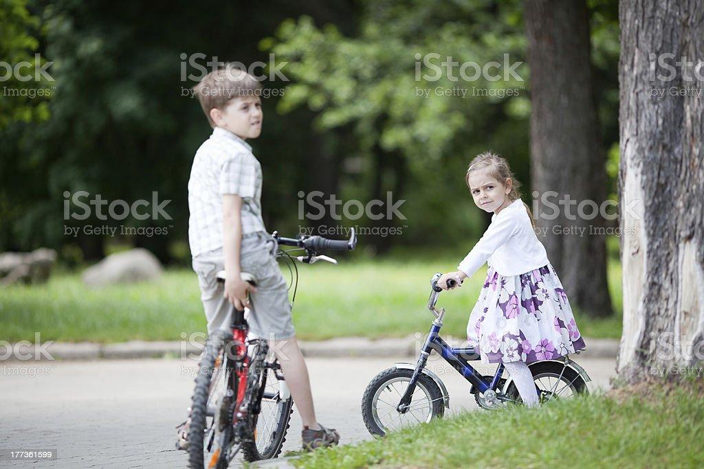 Siblings riding bicycles royalty-free stock photo