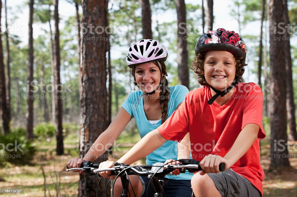 Siblings riding bicycles stock photo