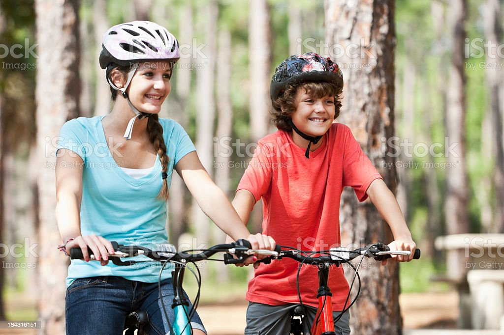 Siblings riding mountain bikes stock photo