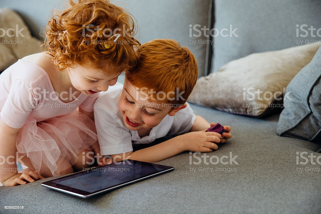 Siblings Sharing Digital Tablet stock photo