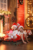 Siblings sisters in santa hats near  fireplace on Christmas ligh