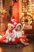 Siblings sisters in santa hats near  fireplace on Christmas ligh