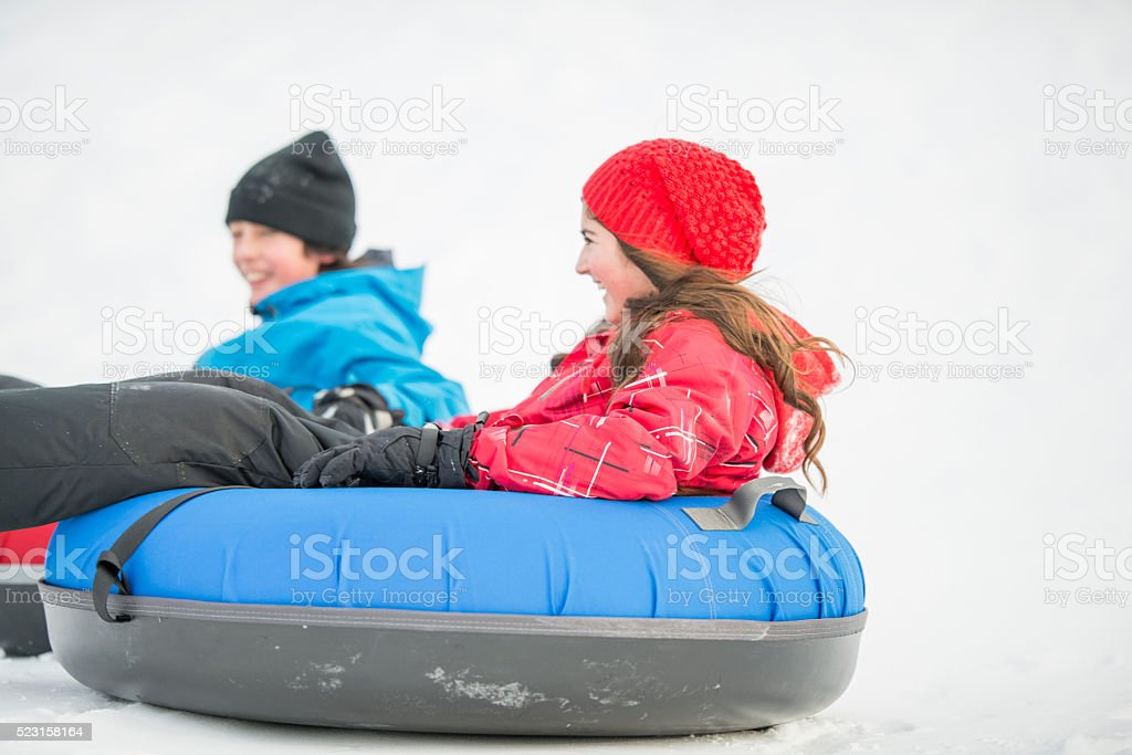 Siblings Sledding on Winter Vacation stock photo