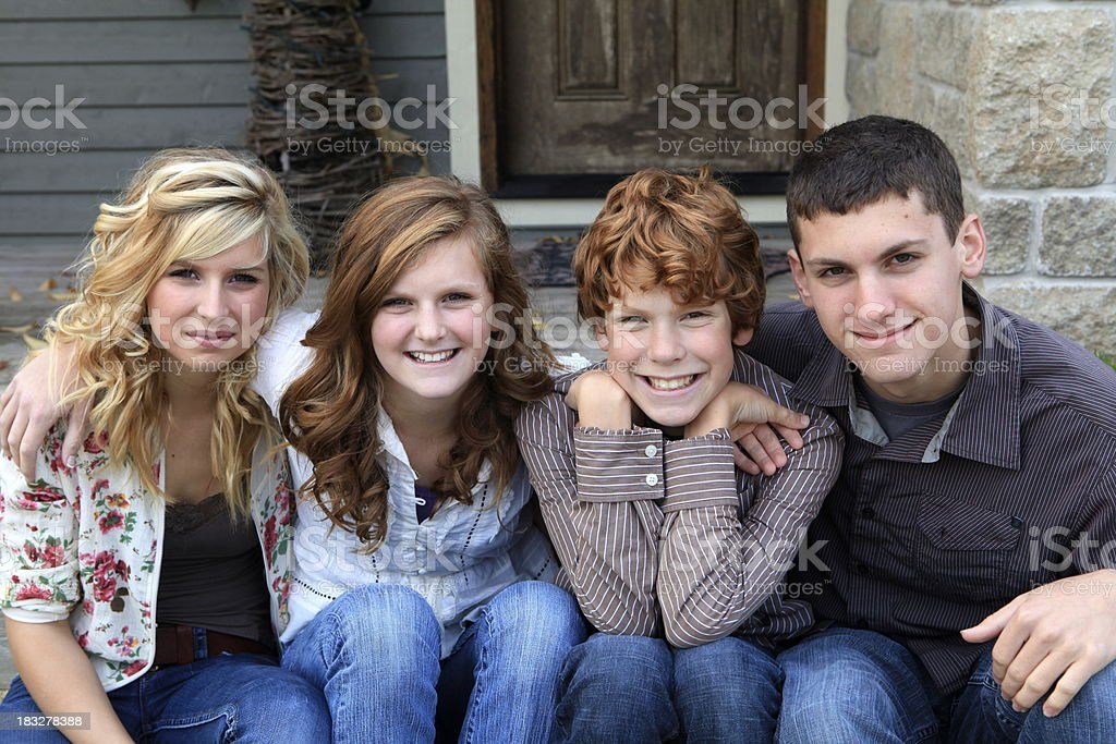 Siblings Together In Front of Their Home royalty-free stock photo