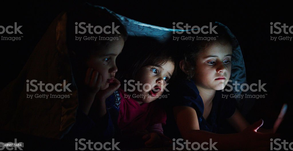 Siblings Watching a Movie Under a Blanket stock photo