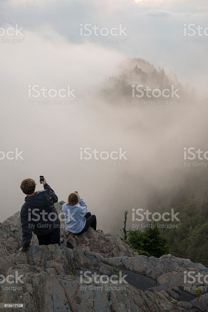 Siblings with smartphones at Mount LeConte, Smoky Mountains stock photo
