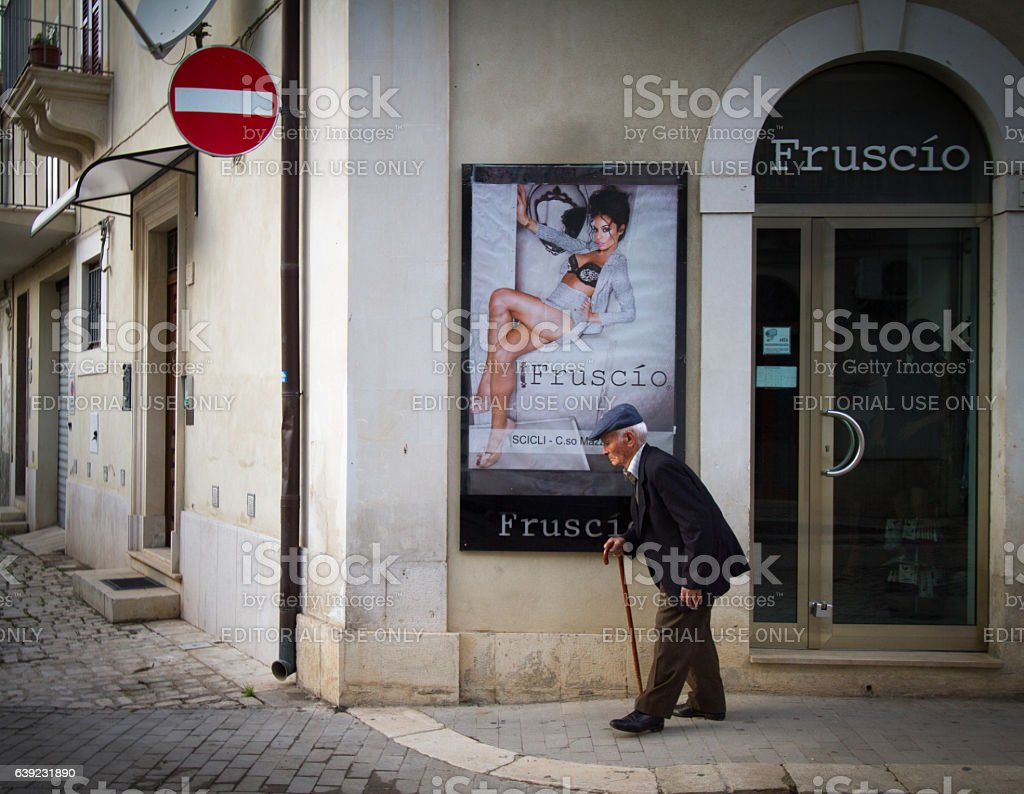 Sicily: Bent Senior Man with Cane and Sexy Poster Ad stock photo