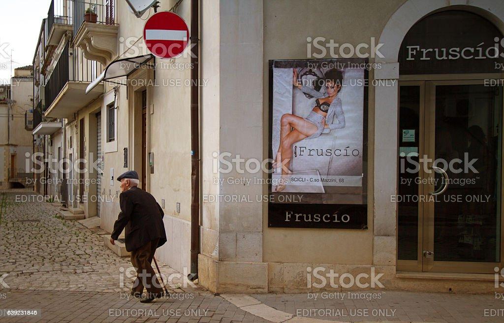 Sicily: Bent Senior Man with Cane Near Sexy Poster Ad stock photo
