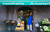 Sicily: Grocer in Blue Apron in Doorway of Colorful Mini-Market