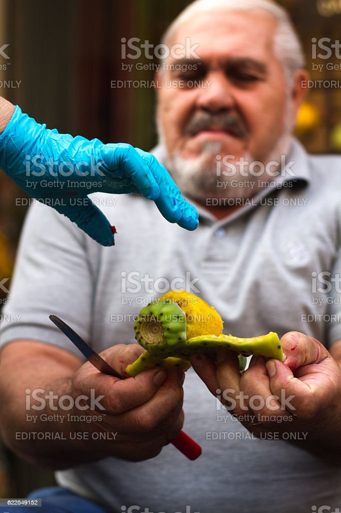 Sicily: Man Peeling Prickly Pear Fruit; Gloved Hand Reaching stock photo