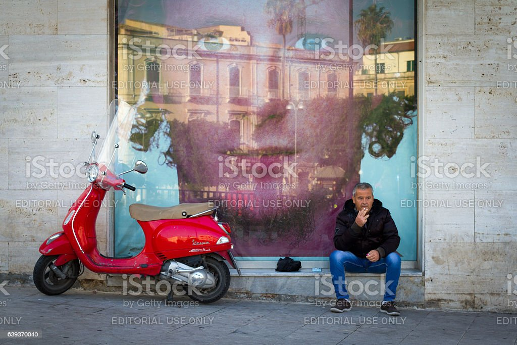 Sicily: Man Sits Smoking Near Vintage Vespa and Huge Advertisement stock photo