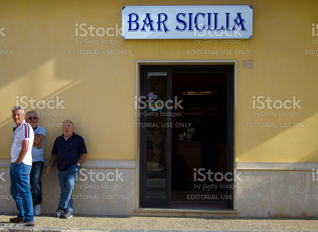Sicily Scene: Men Leaning Against Wall Outside 'BAR SICILIA' stock photo