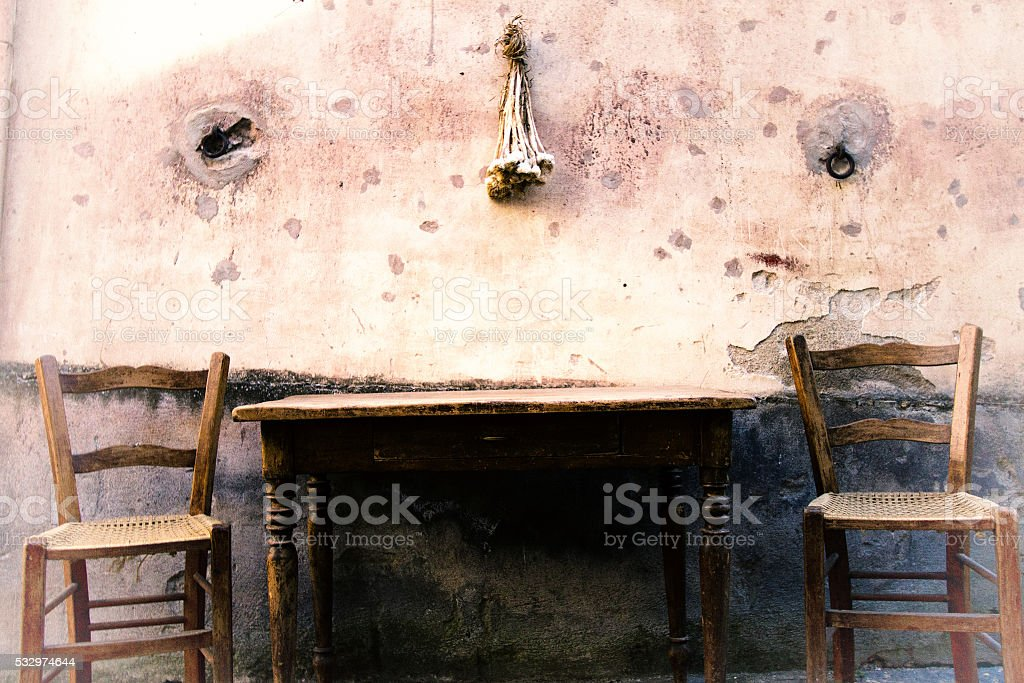 Sicily Style: Rustic Chairs and Table, Mottled Wall, Hanging Garlic stock photo