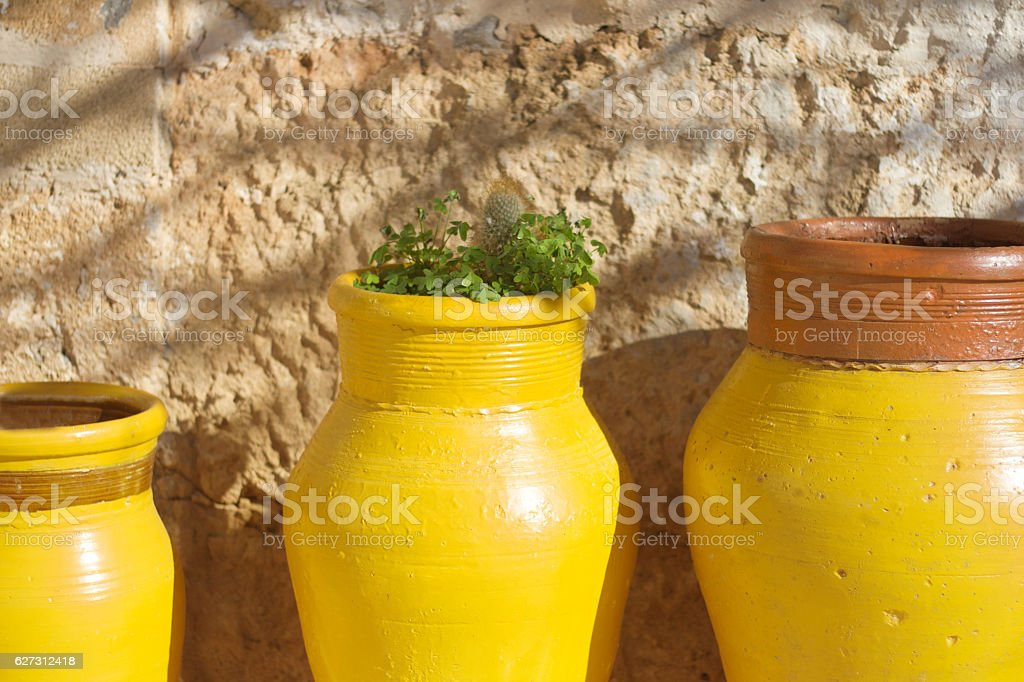 Sicily Style: Trio Rustic Yellow Pots, Sunshine, Old Stone Wall stock photo
