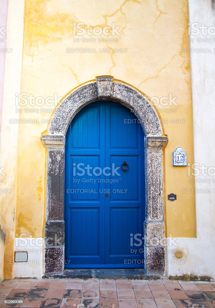 Sicily Style: Vibrant Blue Arched Door in Bright Yellow Wall stock photo