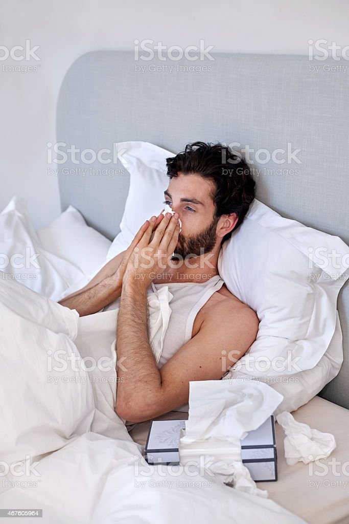 A sick and depressed man with tissues in bed stock photo