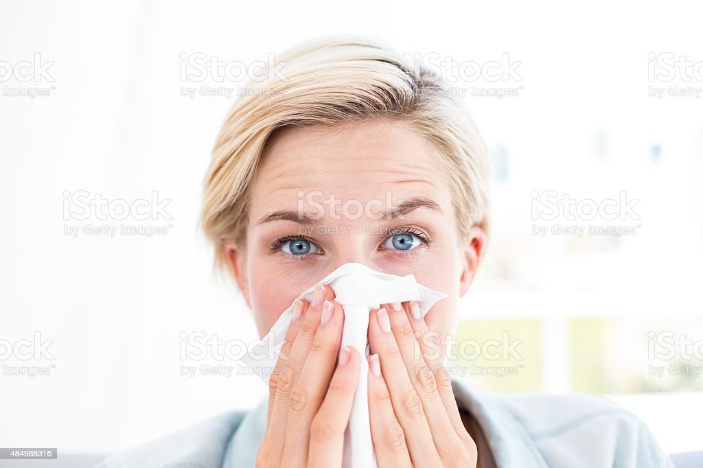 Sick blonde woman blowing her nose stock photo