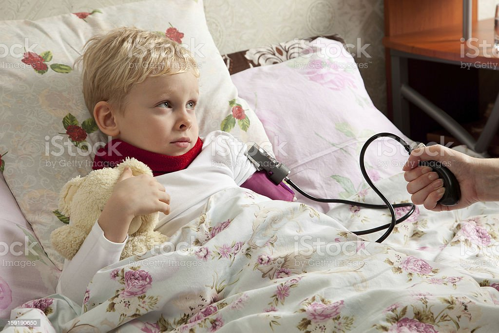 Sick boy is laeing in bed royalty-free stock photo