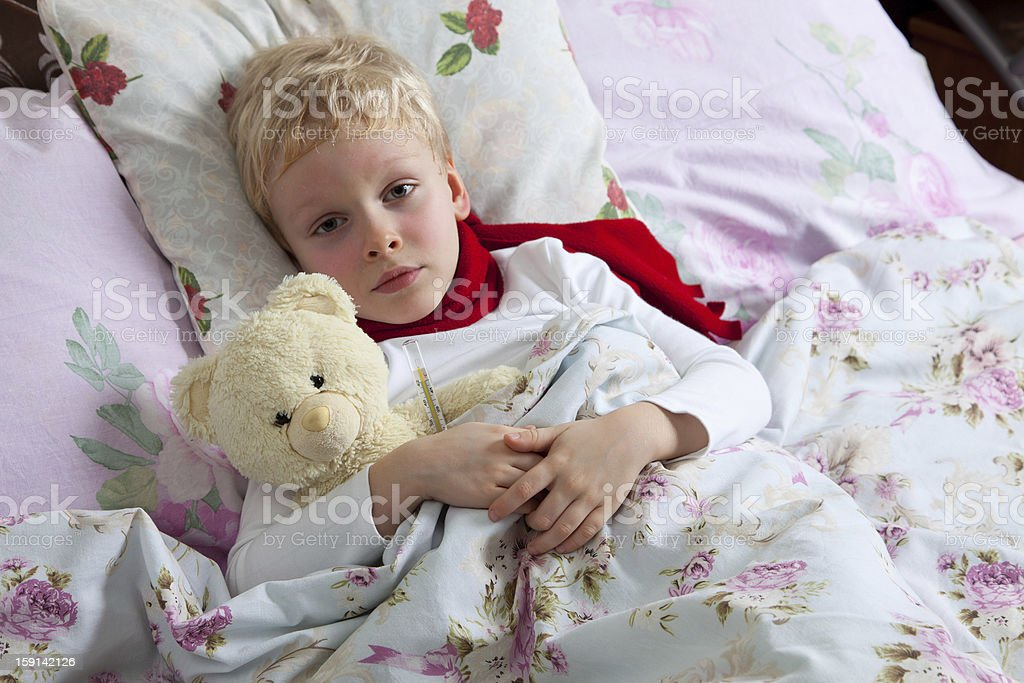 Sick boy lies in bed royalty-free stock photo