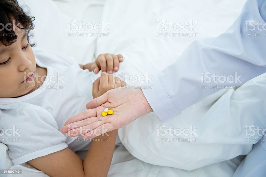 Sick boy taking medicine stock photo