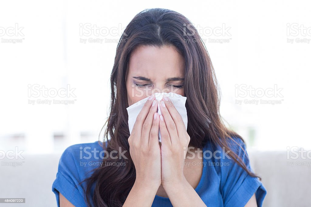 Sick brunette blowing her nose stock photo