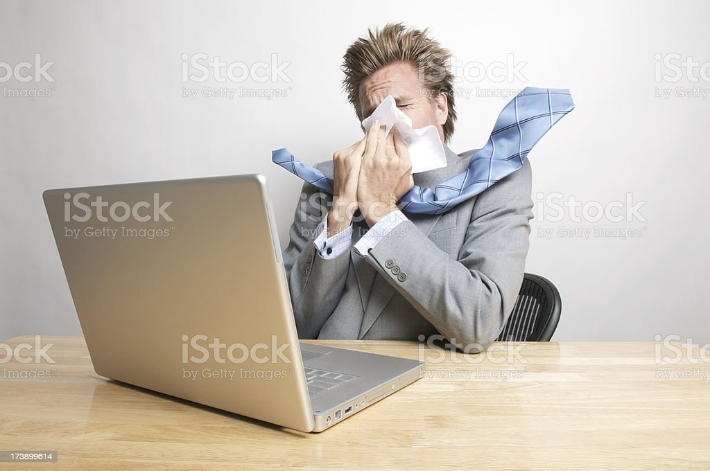 Sick Businessman Blowing His Nose Sitting at Office Desk stock photo