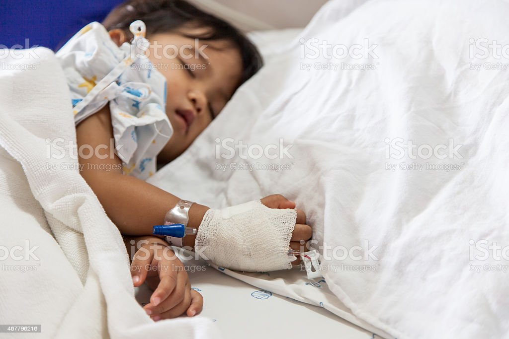 Sick child asleep in hospital bed with gown and canula stock photo